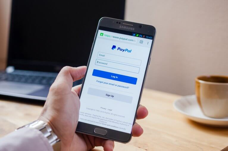 Man logging into PayPal on a smartphone