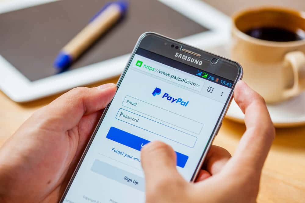 Person logging into PayPal on a smartphone