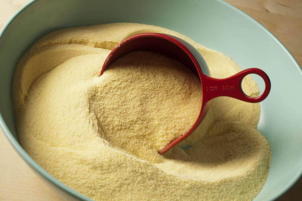 Semolina flour in a bowl with a measuring cup