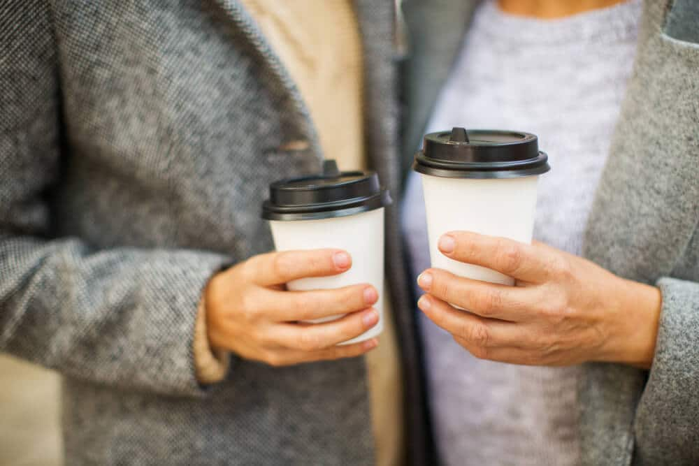 Two senior citizens stand with their cups of discounted coffee.