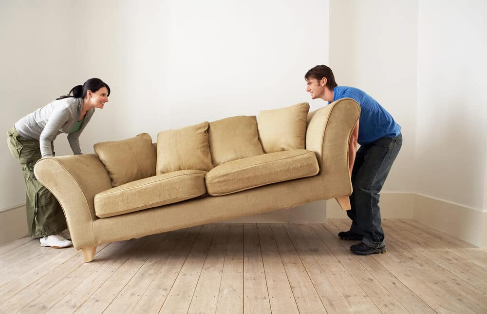 A man and woman move a used couch.