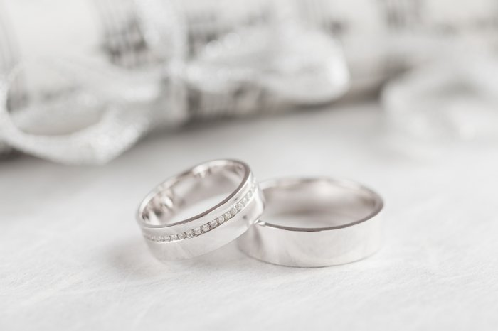 Two white gold rings resting on a white table