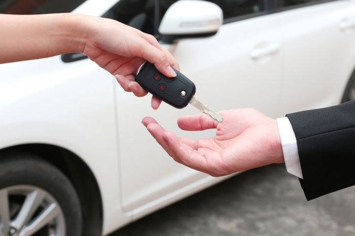 Female hand giving a key for buyer or rental car.