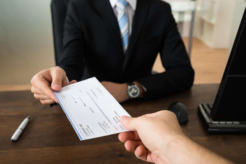 businessperson handing off a cashiers check