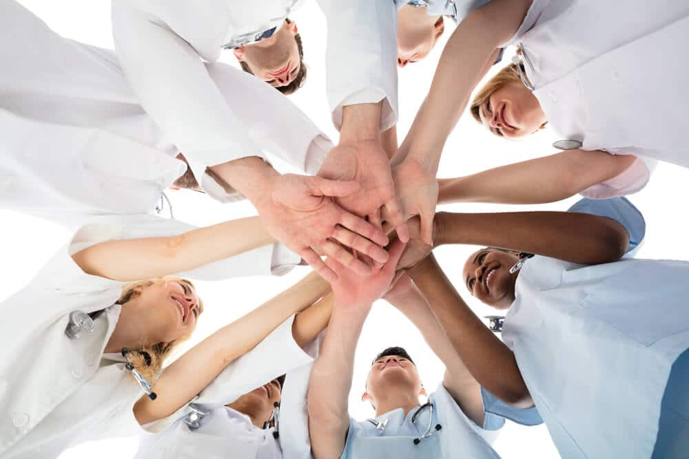 medical team stacking hands in a huddle