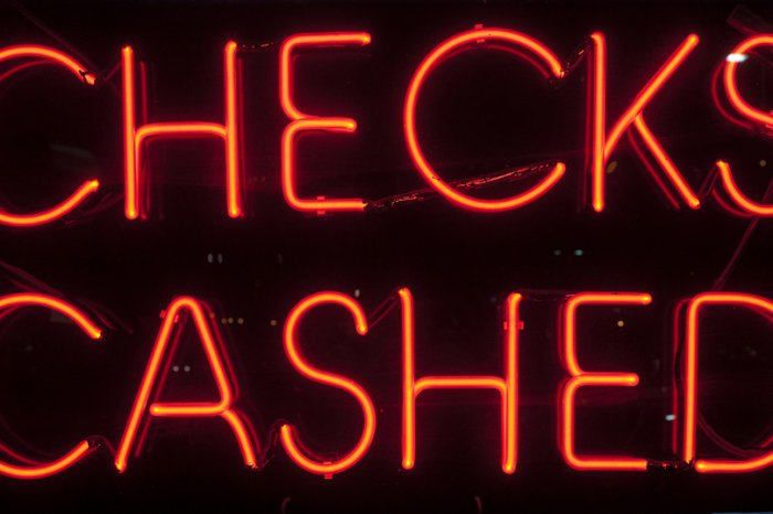 neon sign that says checks cashed