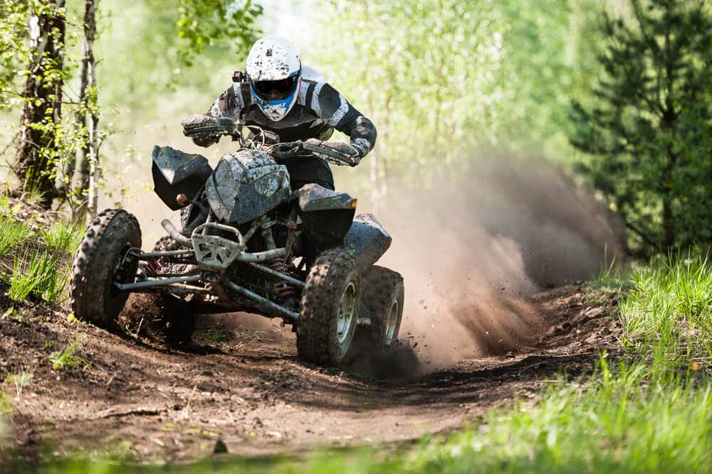 a person in full gear riding an ATV on a trail in the forest