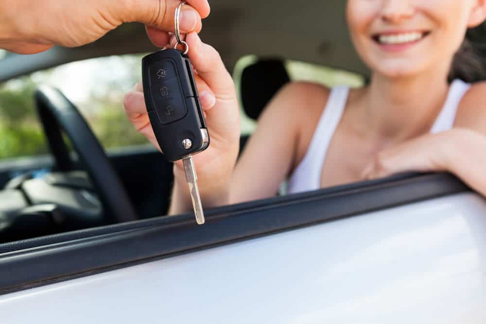 A young woman accepts keys to a car