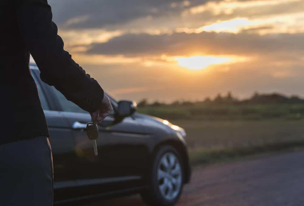 woman holding a car key in front of a car at sunset