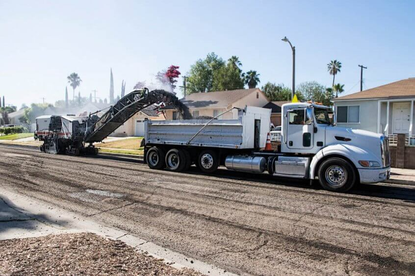 A truck getting loaded with asphalt millings.