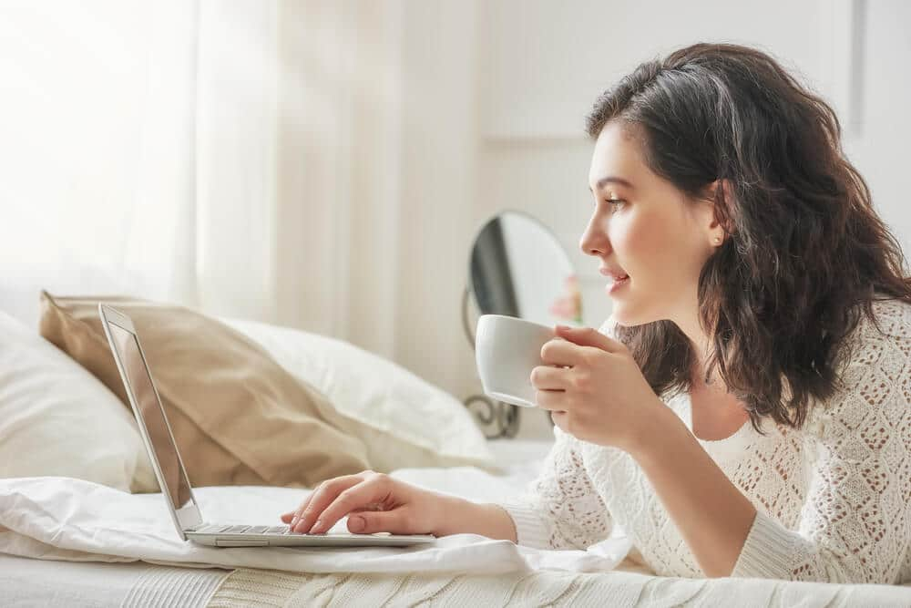 A woman sips coffee as she browsing the list of instant approval credit cards on her laptop.
