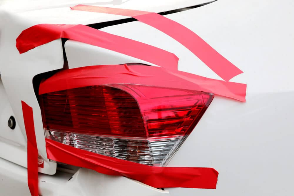 Picture of a car with light rear quarter panel damage and red duct tape over a tail light.