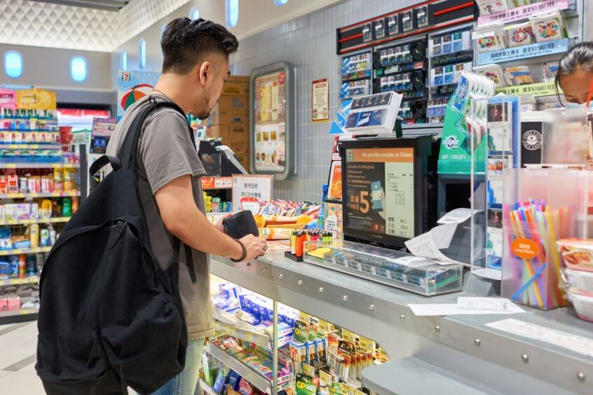 A man waits at the counter of a convenience store while having his check cashed.