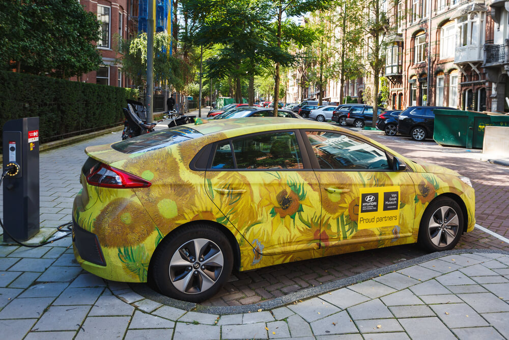 a compact car wrapped in advertising for a museum