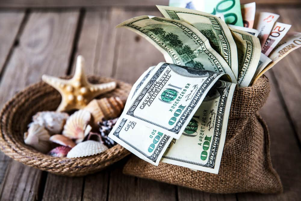 A bag filled with 100 dollar bills sits next to a basket of seashells